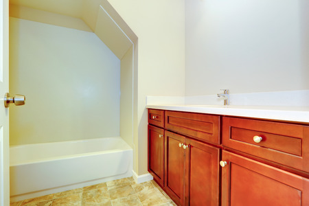 Empty bathroom interior with vanity cabinet and bath tub with vaulted ceiling