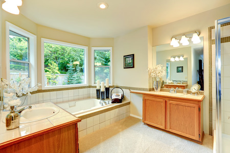 Bathroom with tile trimmed bath tub and two vanity cabinets