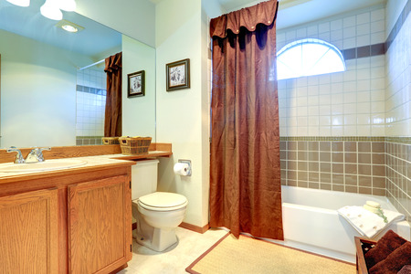 Bathroom with tile wall trim and arch window. Bath tub decorated with brown curtain