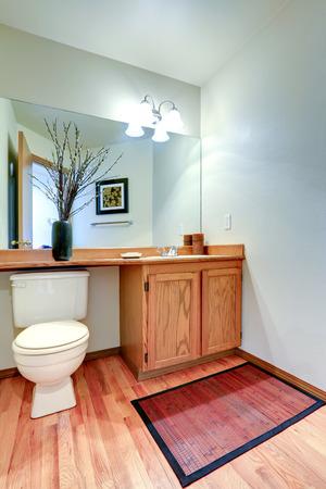 bathroom mirror: Bathroom vanity cabinet with counter top and mirror. New hardwood floor and light tone walls