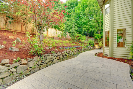 Walkout patio with sitting area and backyard leveled landscape design with stones.  Tile walkway Stock Photo