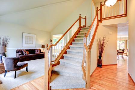 Bright ivory house interior with high vaulted ceiling. View of staircase with carpet steps and wooden railings