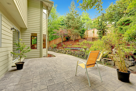 house siding: Walkout patio with sitting area and backyard leveled landscape design Stock Photo