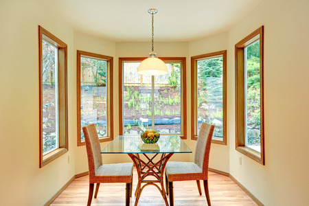 dining table and chairs: Cozy dinig area by the round wall with windows. Glass top dining table with wicker chairs Stock Photo