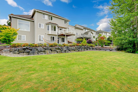Big house with walkout deck and back yard landscape with lawn and stone wall Stock Photo