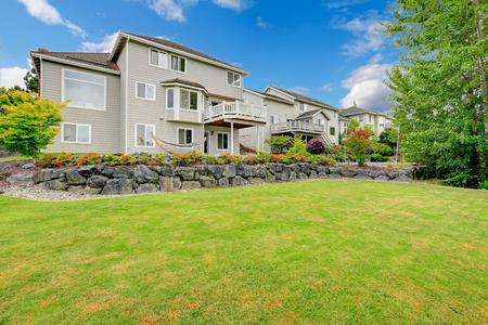 Großes Haus Mit Ausstand Deck Und Hinterhof Landschaft Mit Rasen Und  Steinmauer Standard Bild