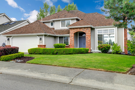 Classic house exterior with brick trimmed entrance porch, green lawn and trimmed hedges