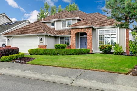 Klassiek huis exterieur met bakstenen getrimd entree veranda, groen gazon en heggen