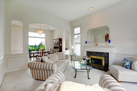 granite wall: Bright living room with granite background fireplace, striped furniture set and glass top coffee table