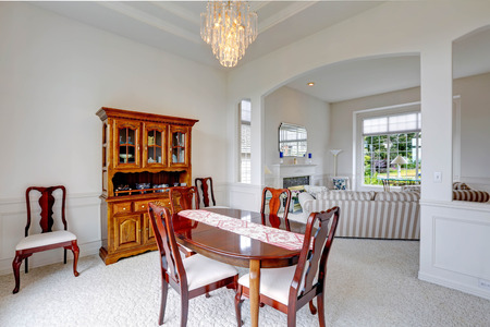 Bright Dining Room With Carved Wood Cabinet Wooden Table And Chairs View Of Living
