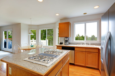 stoves: Spacious kitchen room with maple strorage combination and granite top kitchen island with built in stove Stock Photo