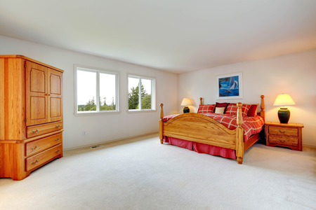 Spacious master bedroom interior with wooden bed and wardrobe