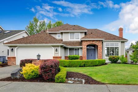 zakelijk: Klassiek huis exterieur met bakstenen getrimd entree veranda, groen gazon en geschoren heggen. Garage met oprit Stockfoto