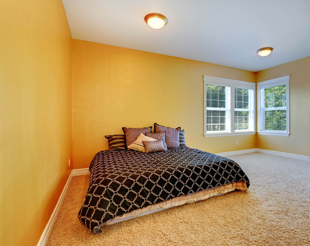 Empty bedroom inteiror with queen size bed. Room in bright yellow color with beige soft carpet floor Stock Photo