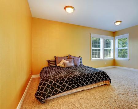 queen bed: Empty bedroom inteiror with queen size bed. Room in bright yellow color with beige soft carpet floor Stock Photo