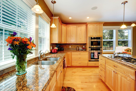Maple storage combination with shiny granite counter top decorated with fresh flowers.