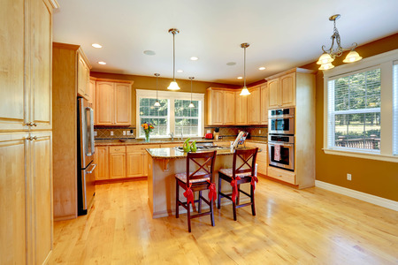 Shiny kitchen room with maple storage combination, kitchen island and stools