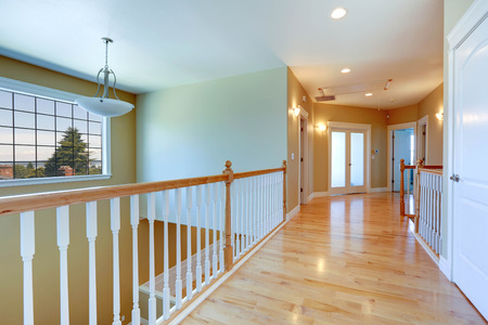 upstairs: Upstairs hallway with shiny hardwood floor and white railings