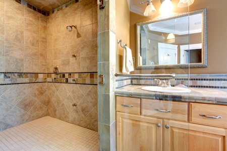 Luxury bathroom interior with tile wall trim, open shower and maple vanity cabinet Stockfoto