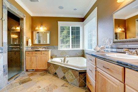 Luxury bathroom interior in mustard color with corner bath tub and two bathroom vanity cabinets