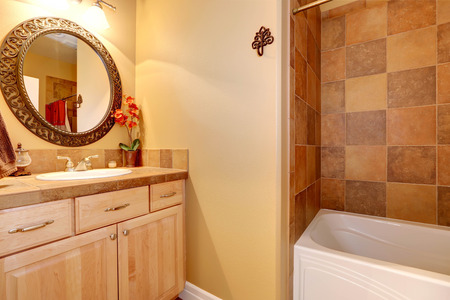Warm tones bathroom interior with tile wall trim and maple vanity cabinet with mirror Stock Photo