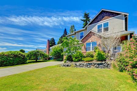 Huis buitenkant met bakstenen muur bekleding, garage en oprit. Voortuin landschap met gazon, decoratieve bomen en stenen bekleding