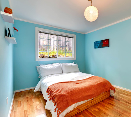 Cozy bedroom in light blue color with hardwood floor and wooden single bed with white and orange bedding