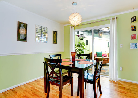Cozy dining room with white and mint color walls with dark brown dining table set. Room has exit to backyard Zdjęcie Seryjne