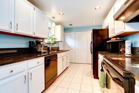 black appliances: Interno Cucina con armadi bianchi, ripiani neri ed elettrodomestici neri