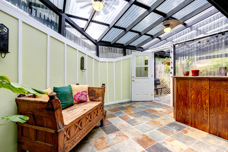 Bright mint room with glass ceiling, light mint walls and tile floor. Room furnished with carved wood bench. Room has exit to backyard