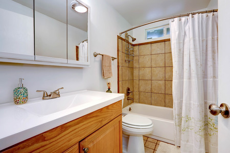 white trim: Bathroom inteiror in old house with tile wall trim, wooden vanity cabinet with white sink and mirror Stock Photo