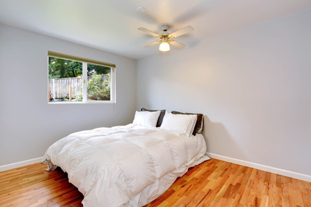 image size: Bedroom interior with hardwood floor,  queen size bed in refreshing white bedding Stock Photo