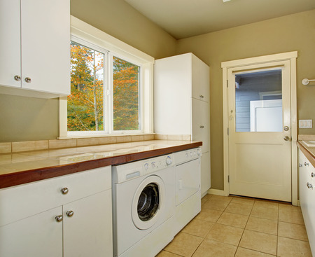 Laundry room with cabinets tile counters washer and dryer.