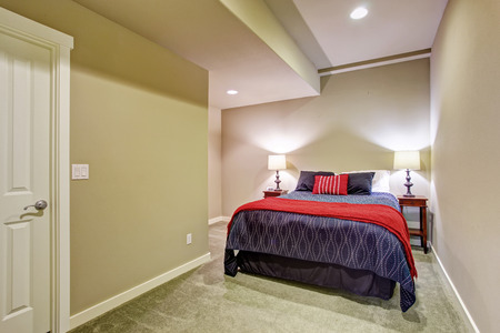 Basement guest bedroom without windows with blue and red bedding. photo