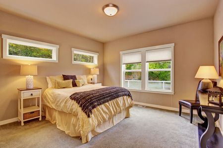 designer chair: Bright bedroom with yellow queen sized bed carpet and windows. Stock Photo