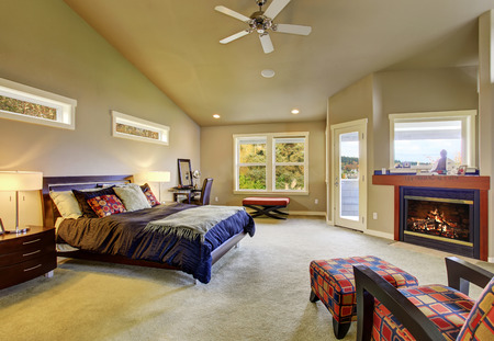 master bedroom: Large master bedroom with windows fireplace and colorful furniture.