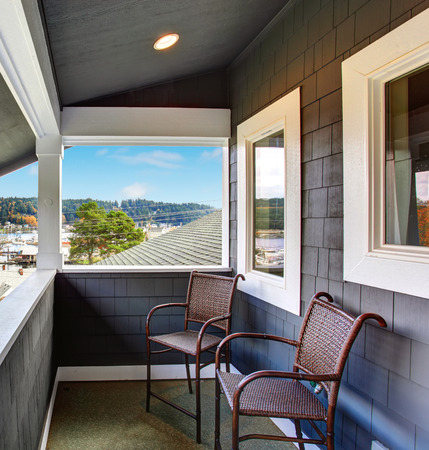 gig: Covered small porch of dark blue Northwest home in Gig Harbor.