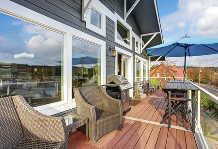 wooden deck: Northwest traditinal wooden deck with large windows, chairs and tables. Stock Photo