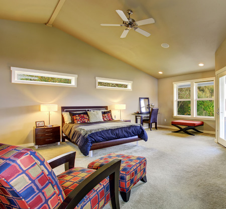 master bedroom: Large master bedroom with windows, fireplace, and colorful furniture.