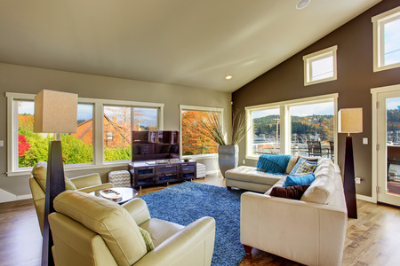 Huge living room interior with many windows and white leather sofa
