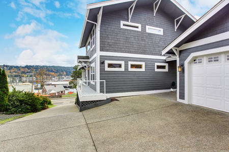 garage on house: Large gray house with garage, driveway, and porch. Stock Photo