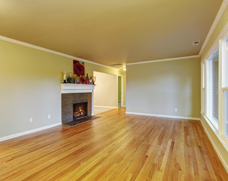 fireplace family: Simplistic family room with fireplace, hardwood floor, and window. Stock Photo