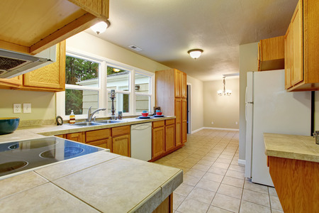 kitchen cabinets: Authentic kitchen with tile floor, windows, and wooden cabinets.