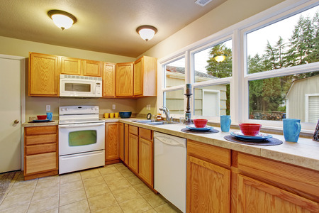 cabinets: Authentic kitchen with tile floor, windows, and wooden cabinets.