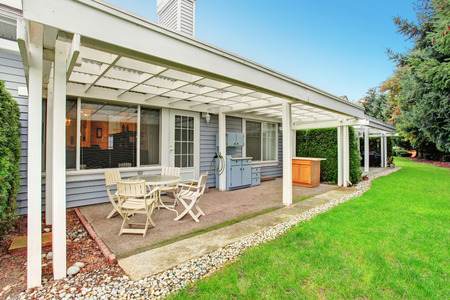 porches: Simple covered back patio with cabinets, chairs, and a table.