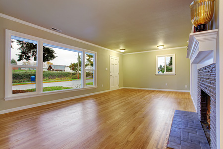hardwood: Simplistic family room with fireplace, hardwood floor, and window. Stock Photo