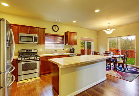 kitchen island: Classic kitchen with hardwood floor, island, and connected dinning room.