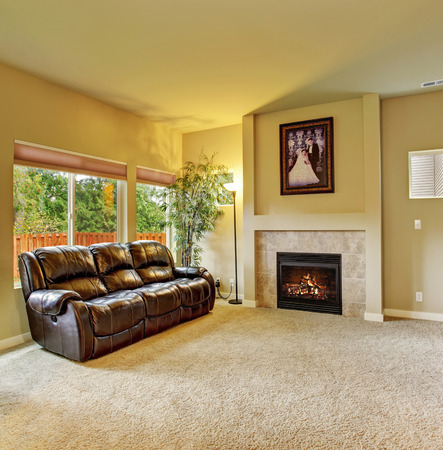 Cozy living room with carpet, fireplce, and leather sofa.