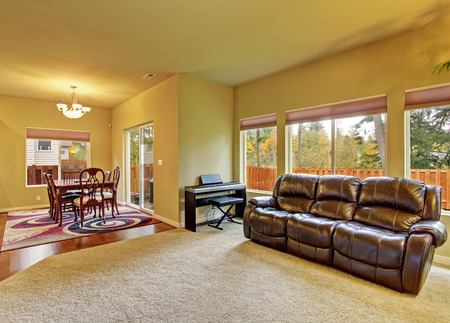 leather sofa: Cozy living room with carpet, fireplce, leather sofa, and connected dinning room.