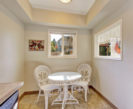 table and chairs: Extra dinning area with white table and chairs, and two windows.